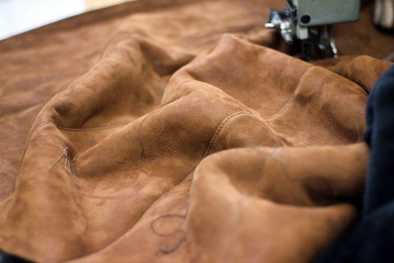 Mit einer Nähmaschine wird braunes Kunstleder verarbeitet
