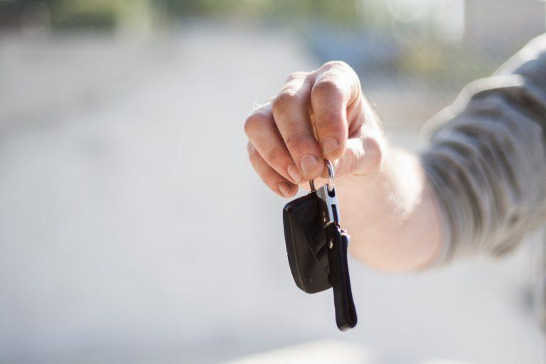 Ein Mann übergibt einen Autoschlüssel mit einem Schlüsselanhänger aus Kunstleder daran