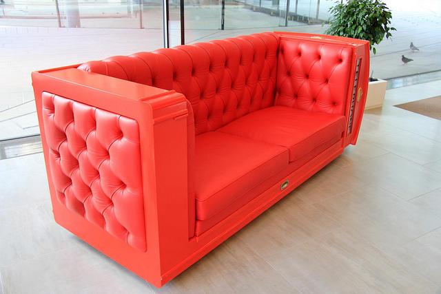 Ein rotes Kunstledersofa steht in einem hellen Raum