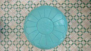 Ein himmelsblauer Pouf steht auf einem Mosaikboden.