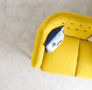 Ein gelbes Sofa ist aus der Vogelperspektive abgebildet. Es hat runde Ecken und ist mit einem blauen Kissen dekoriert.