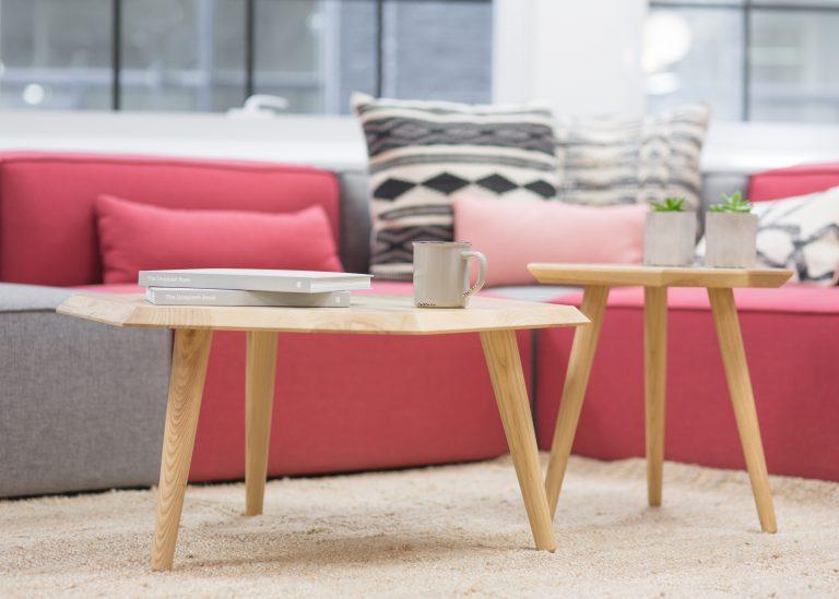 Ein pink-graues Sofa mit vielen gemusterten Kissen steht hinter zwei Holztischen.