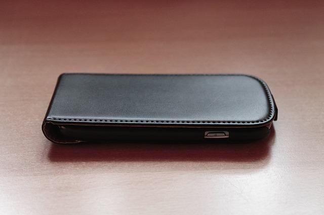 Ein Smartphone in einem Full Case aus schwarzem Kunstleder liegt auf einer Holzoberfläche.