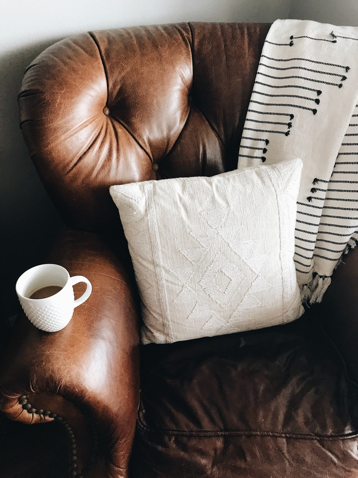 Ein Sofa aus braunem Kunstleder mit Kissen und auf dessen Armlehne eine Kaffeetasse steht.