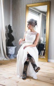 Eine Frau sitzt in einem Hochzeitskleid und Cowboyboots auf einem weißen Stuhl in einem schlicht eingerichteten Raum.