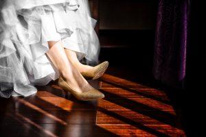 Goldene Kitten Heels zieren die Füße einer Braut mit einem weißen, gerüschtem Kleid.