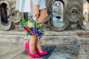 Eine Frau trägt pinke Pumps und hält einen bunten Blumenstrauß in der Hand.