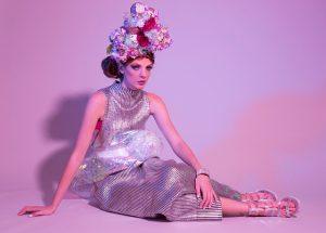 Eine Frau mit einer Blumenkrone und pompösen Make-Up sitzt auf dem Boden und trägt Schuhe und Kleid in Metallic-Optik.