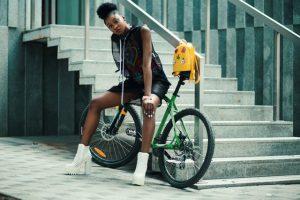 Ein Model in schwarzer Kleidung mit weißen Plateau-Boots sitzt auf einem grünen Fahrrad, welches an einer Treppe angelehnt ist.
