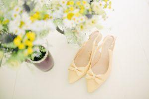helle Kitten Heels mit Schleifen stehen auf einem weißen Untergrund und werden von Blumen umrahmt.