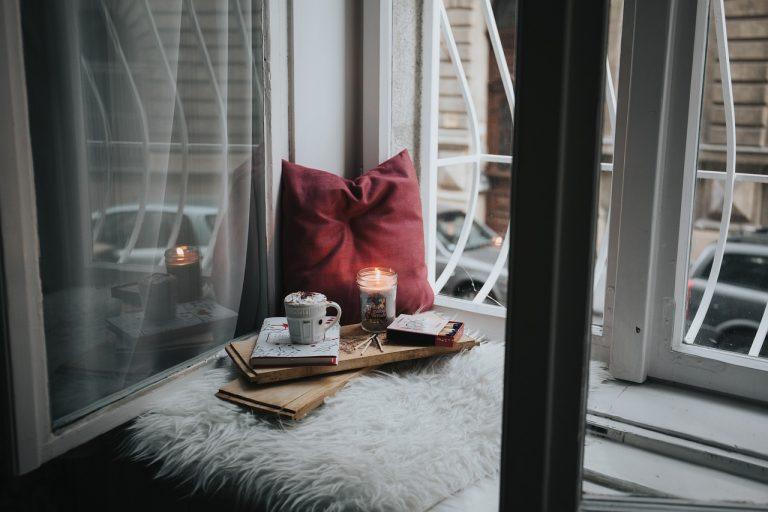 An einem offenen Fenster liegt eine kuschlige Decke und ein rotes Kunstleder-Kissen, davor steht ein Tablett mit Kaffeetasse, Kerze und Lesestoff.