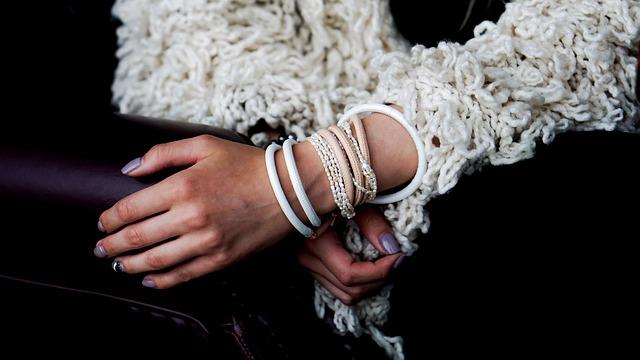 Ein Frauenarm wird von weißen und rosanen Kunstlederarmbändern geziert. Diese sind mit Perlenarmbändern und einer weißen Strickjacke, sowie fein manikürten Nägeln kombiniert.