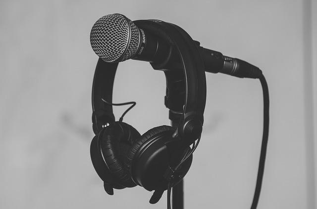 In einem schwarz-weiß Bild hängen dunkle Kopfhörer mit Kunstleder-Ohrmuscheln über einem Mikrofon.