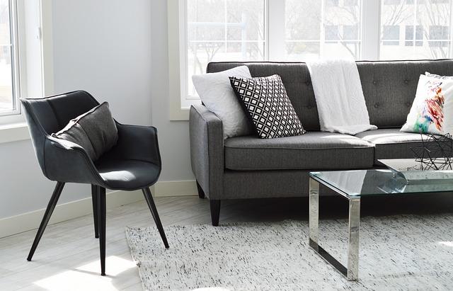 In einem weiß gestrichenen Raum mit Fenstern steht ein graues Sofa mit vielen verschieden gemusterten Kissen. Daneben steht ein dunkelgrauer Stuhl sowie ein Glas-Couchtisch.