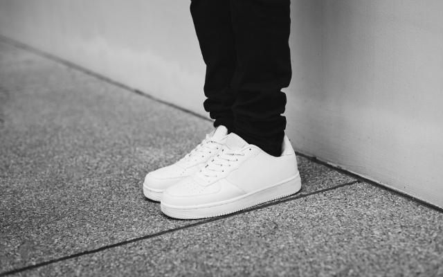 Auf einem grauen Granitboden, vor einer weißen Wand steht eine Person, die eine schwarze Jeans kombiniert mit weißen Dad-Sneakern trägt.