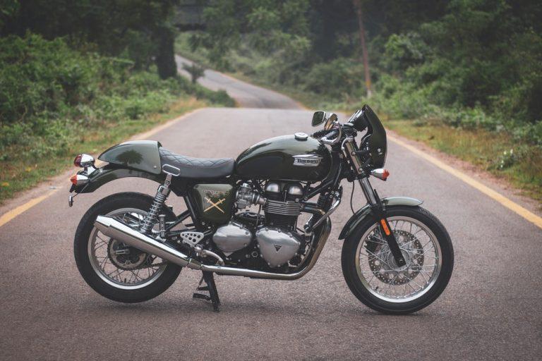 Auf einer Straße umgeben von grünen Pflanzen steht ein dunkles Bike mit einer abgesteppten Motorrad-Sitzbank. im Leder-Look