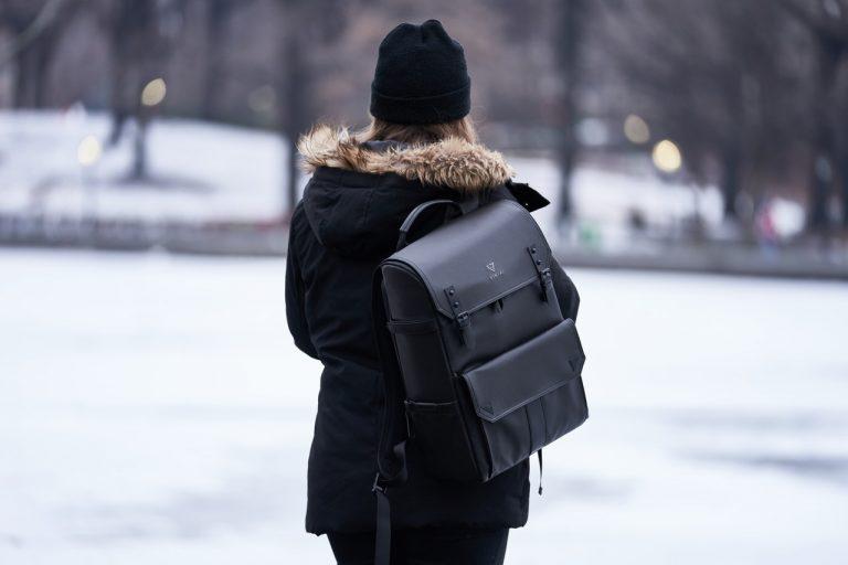 Eine Frau in einem schwarzen Mantel und einer schwarzen Mütze hat uns den Rücken zugewandt. Auf ihrer Schulter trägt sie einen Kunstleder-Rucksack