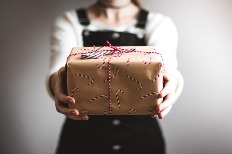 Eine Frau hält ein Geschenk, welches in Packpapier eingepackt ist und mit einer Kordel zusammengebunden wurde.