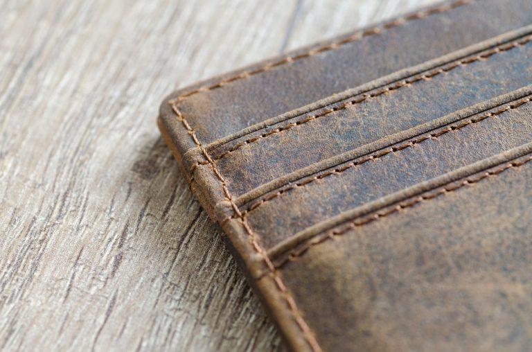 Ein Lederportemonnaie liegt auf einem Holzuntergrund.