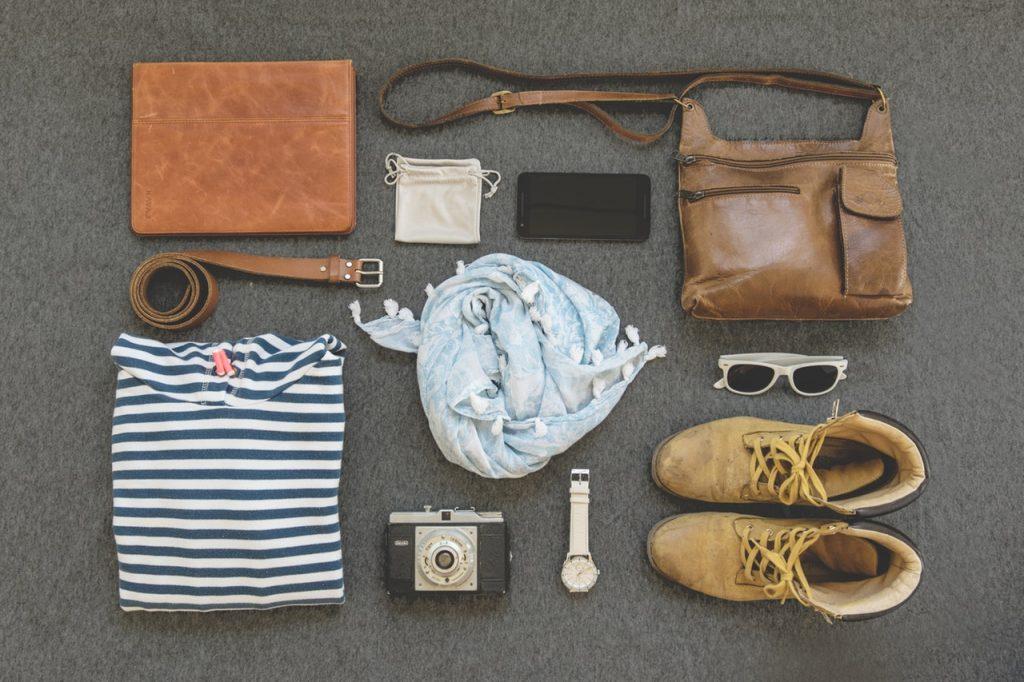 Schuhe, eine Tasche, ein Schal und weitere Reiseutensilien sind auf dem Boden ausgelegt