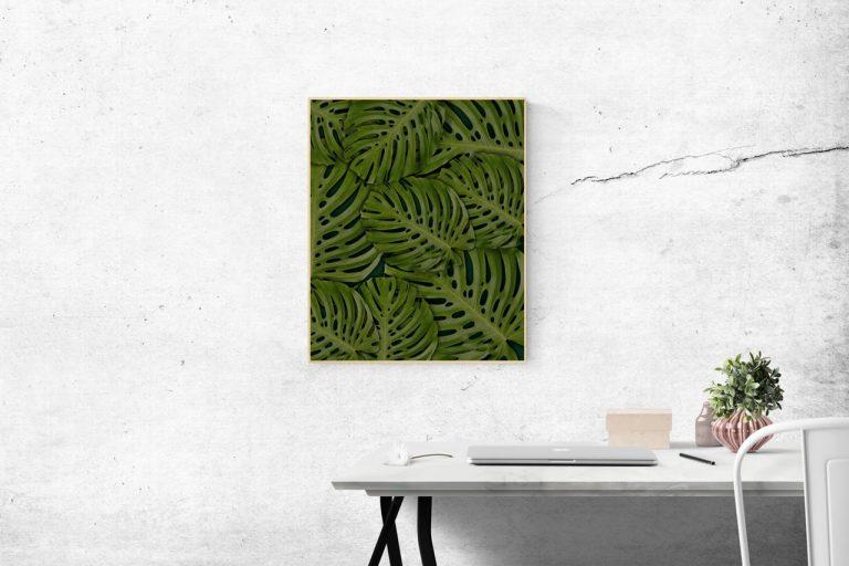 Über einem weißen Schreibtisch hängt ein Bild mit Pflanzenblättern.