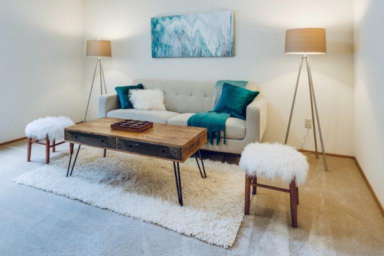 Ein Wohnzimmer ist eingerichtet mit einem Sofa, einem industriell wirkendem Tisch, einigen Lampen, Decken und Kissen.