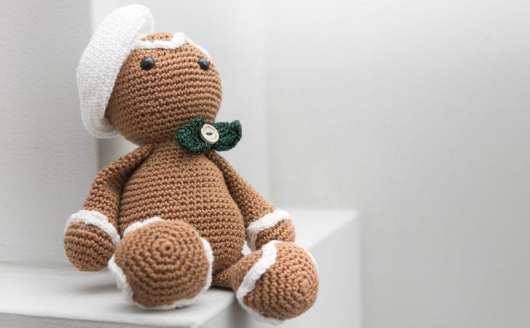 Ein kleiner, gehäkelter Teddy sitzt auf einem weißen Schrank.