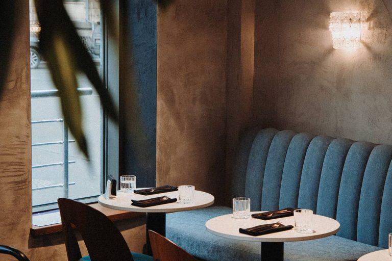 Mit braunem Kunstleder bedeckte Wand in einem Café mit hellblauen Kunstleder-Sitzen