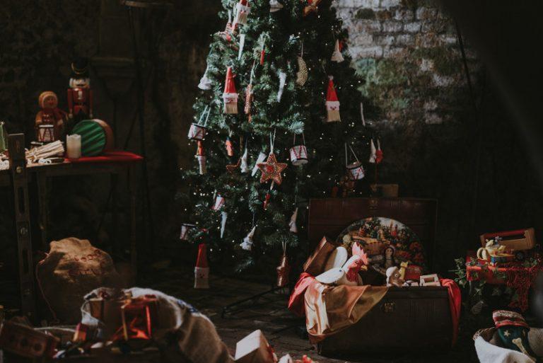 An einem Weihnachtsbaum hängen verschiedene Stofffiguren. Ringsherum stehen mehrere Kisten mit weiteren Dekorationen.
