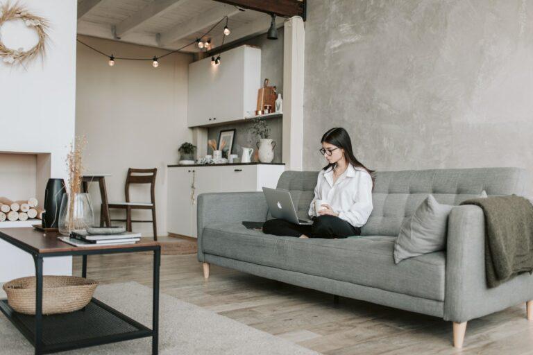 Eine Frau mit einem Laptop auf dem Schoß sitzt auf einem grauen Sofa in einem Zimmer, das im Skandi-Stil eingerichtet ist.